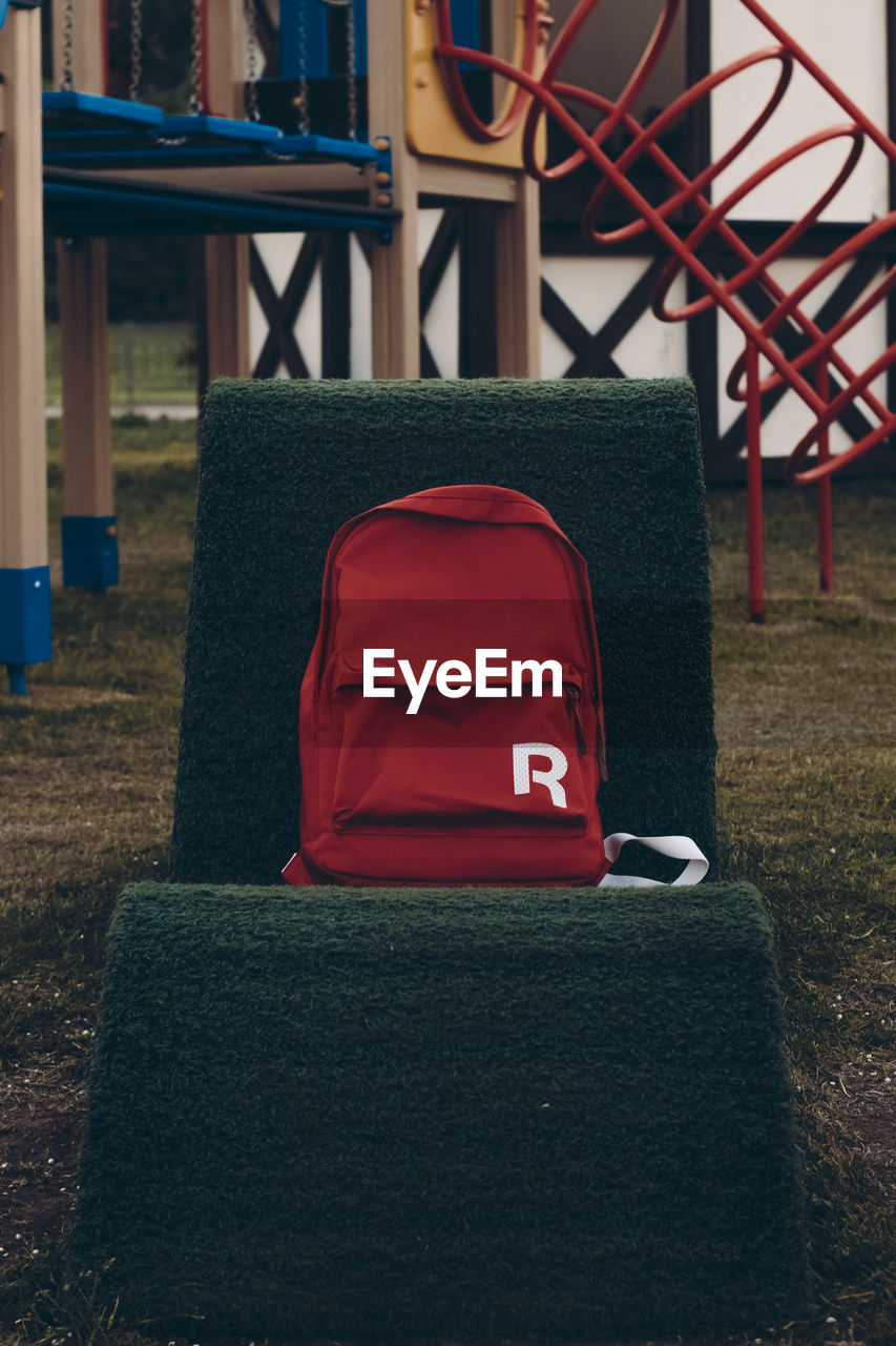 red, seat, chair, no people, empty, focus on foreground, absence, day, field, green color, grass, nature, plant, outdoors, land, metal, table, park, architecture, rear view