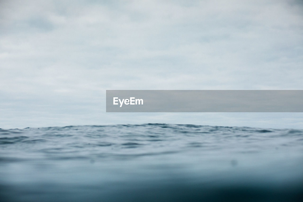 Surface level of sea against cloudy sky