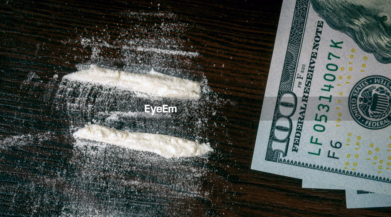 Paper currency and cocaine on table