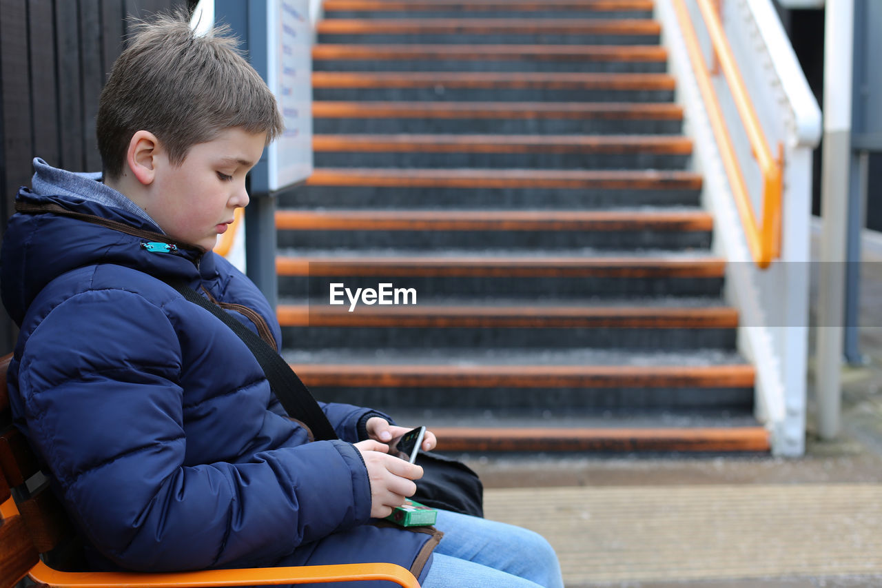 Side View Of Boy Using Mobile While Sitting On Bench At Park