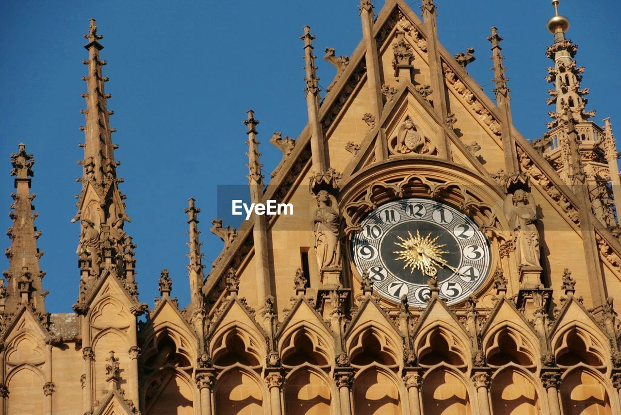 low angle view, time, architecture, religion, ornate, built structure, place of worship, building exterior, clock, day, no people, gold colored, spirituality, history, outdoors, blue, clock face, minute hand, roman numeral, sky