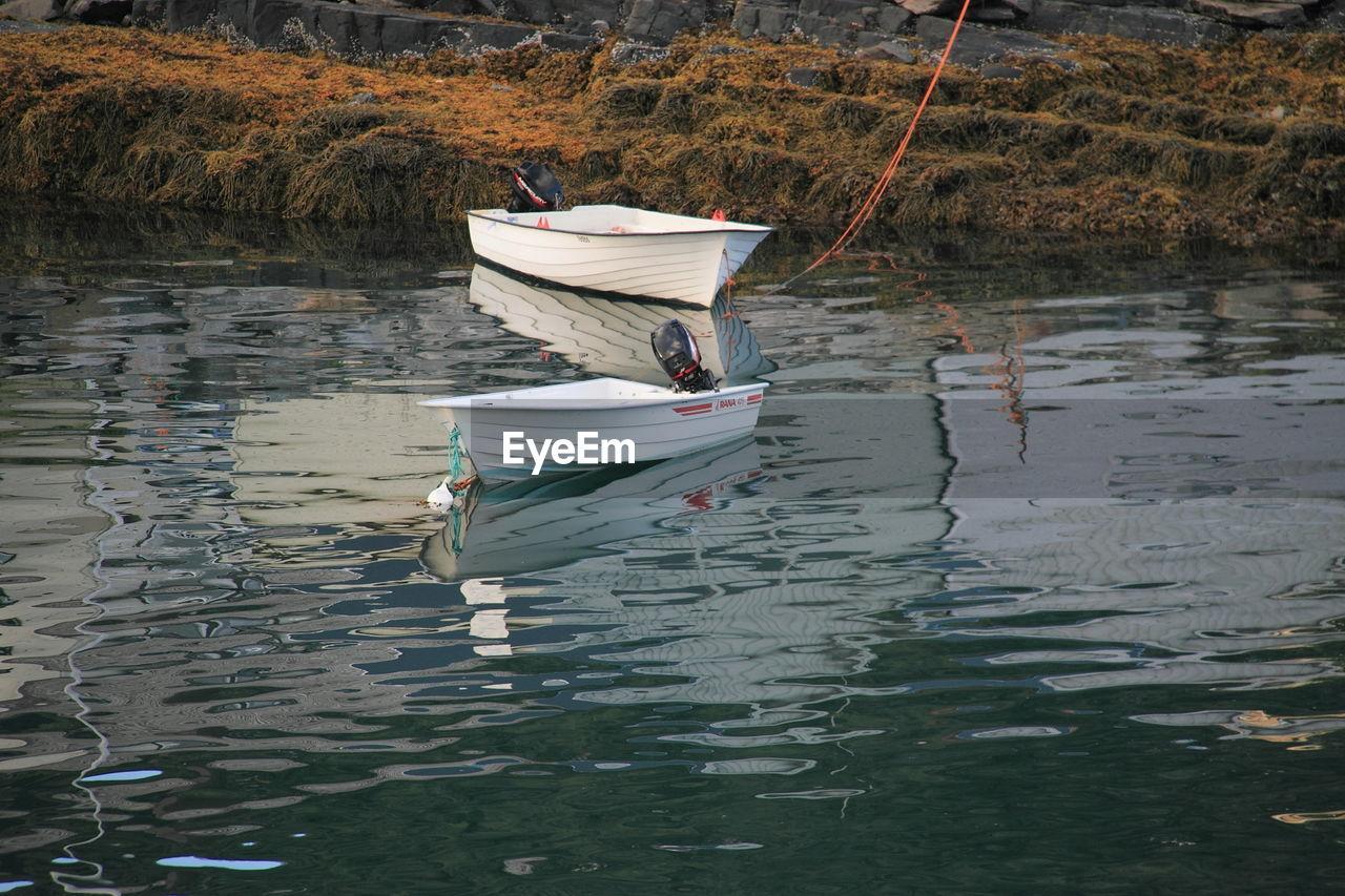 Two Sailboats Anchored At Lake