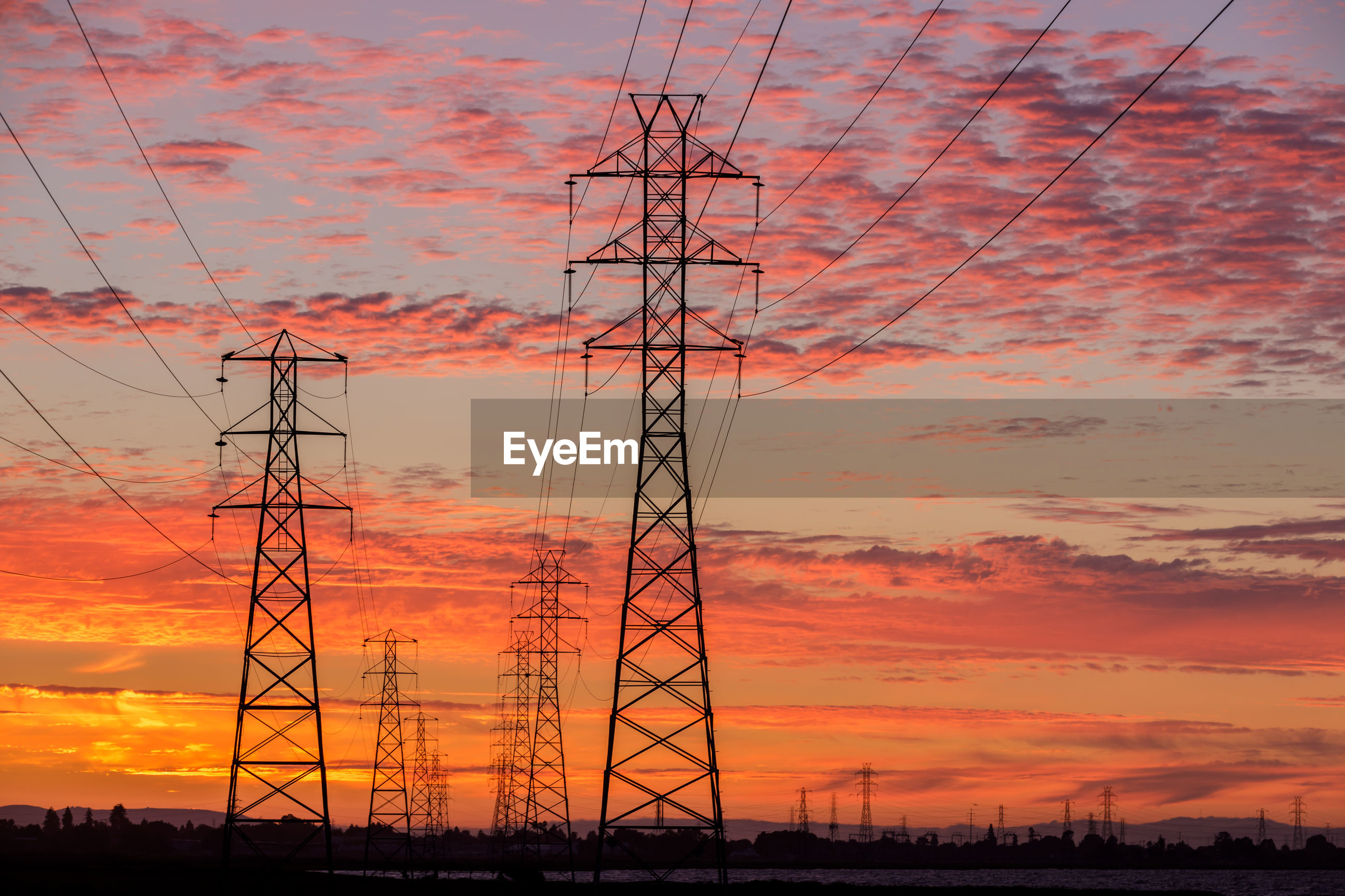 LOW ANGLE VIEW OF SILHOUETTE ELECTRICITY PYLONS AGAINST DRAMATIC SKY