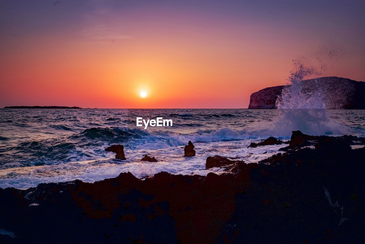 sea, water, sky, sunset, scenics - nature, beauty in nature, motion, horizon over water, wave, beach, horizon, land, rock, orange color, rock - object, splashing, nature, idyllic, tranquil scene, power in nature, sun, no people, outdoors, breaking, flowing water