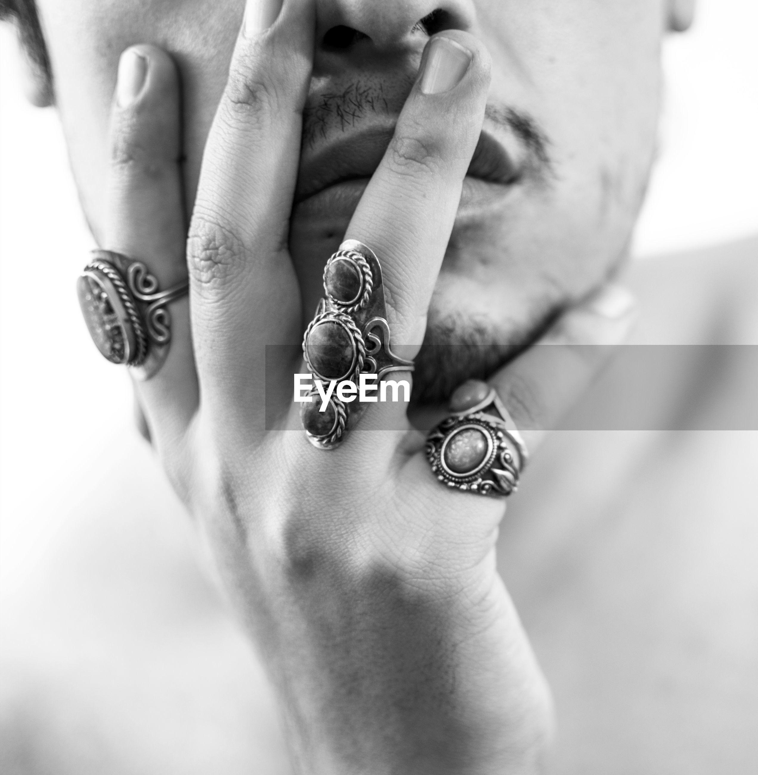 Midsection of shirtless man wearing rings