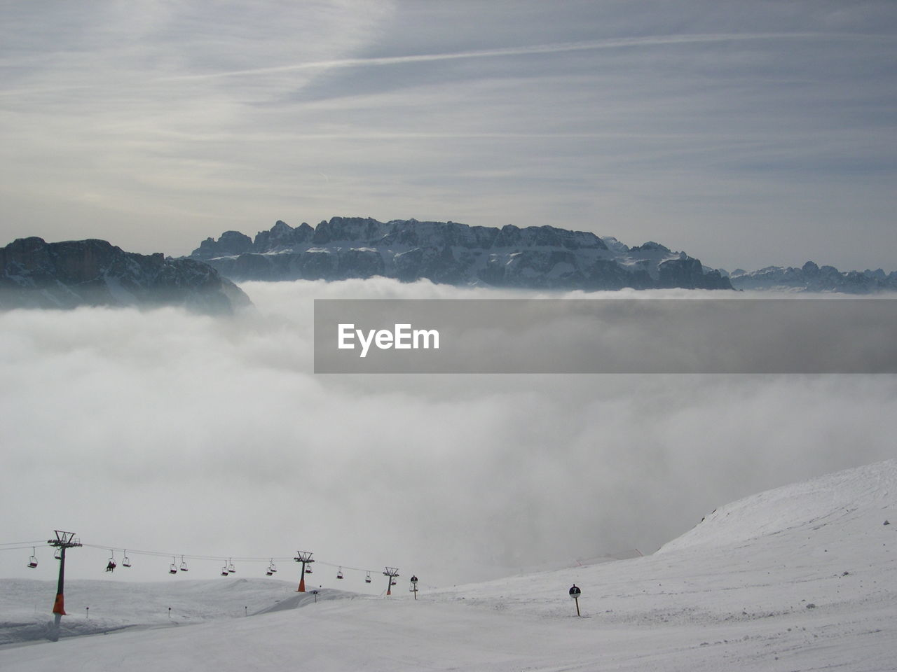 Snowy Landscape Against Clouds Covered Mountains