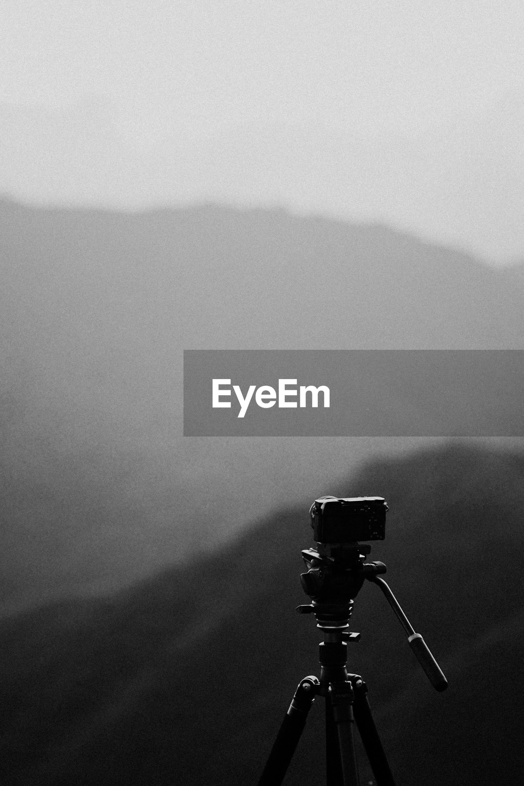 Close-up of camera against sky during foggy weather