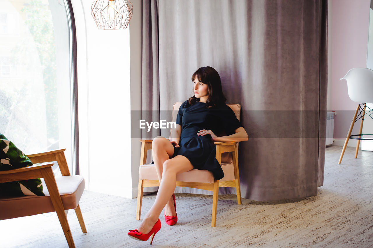 Beautiful Young Woman Sitting On Chair Against Curtain At Home