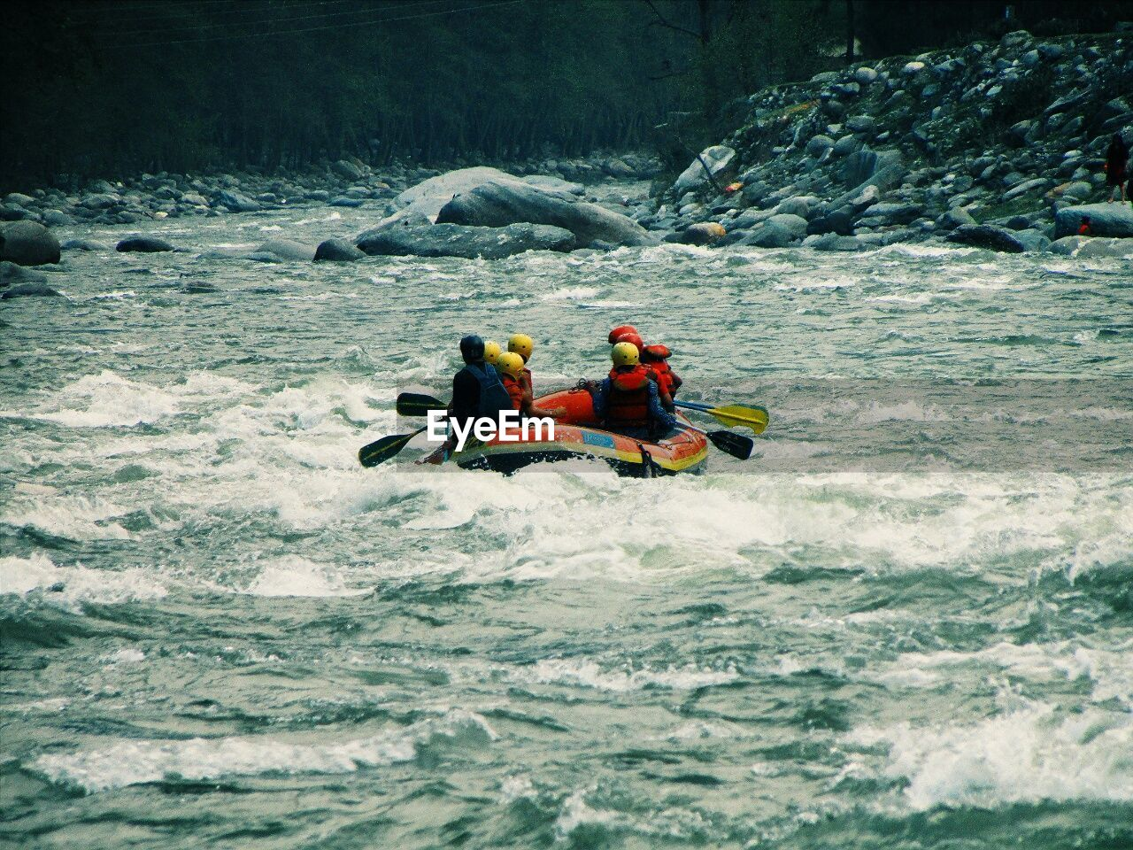 People sailing at inflatable raft in river