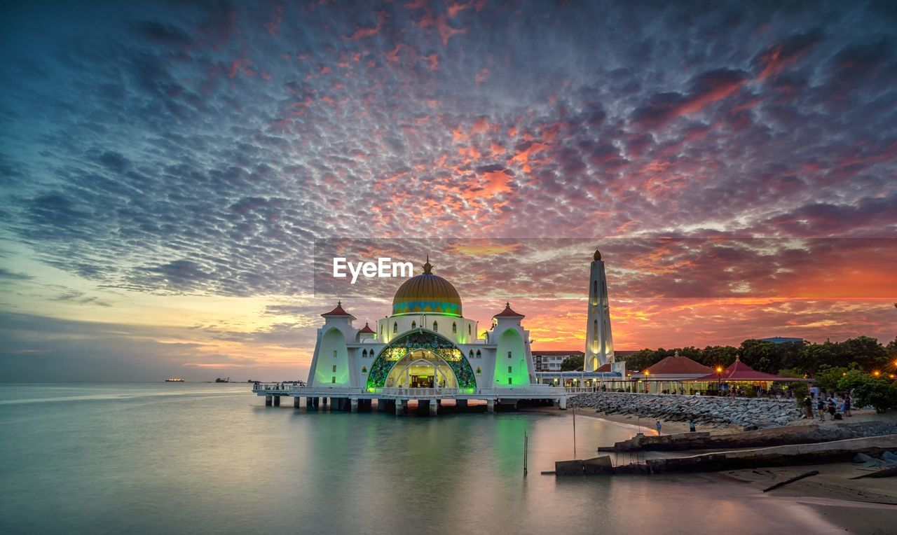 sky, sunset, water, architecture, building exterior, religion, place of worship, built structure, belief, cloud - sky, spirituality, orange color, waterfront, building, nature, dome, outdoors, no people