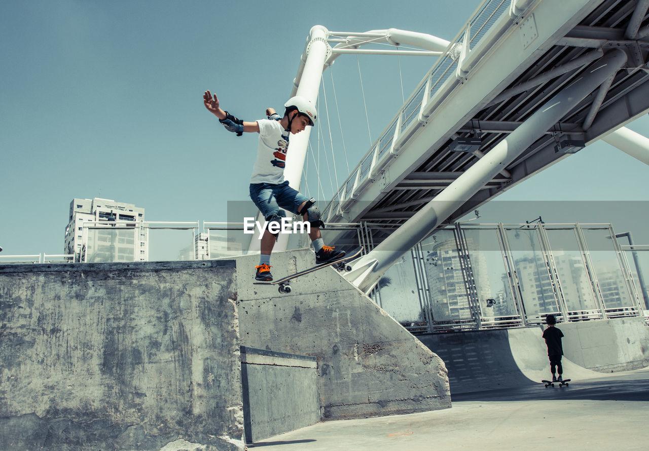 Boy Skateboarding In Park Against Clear Sky