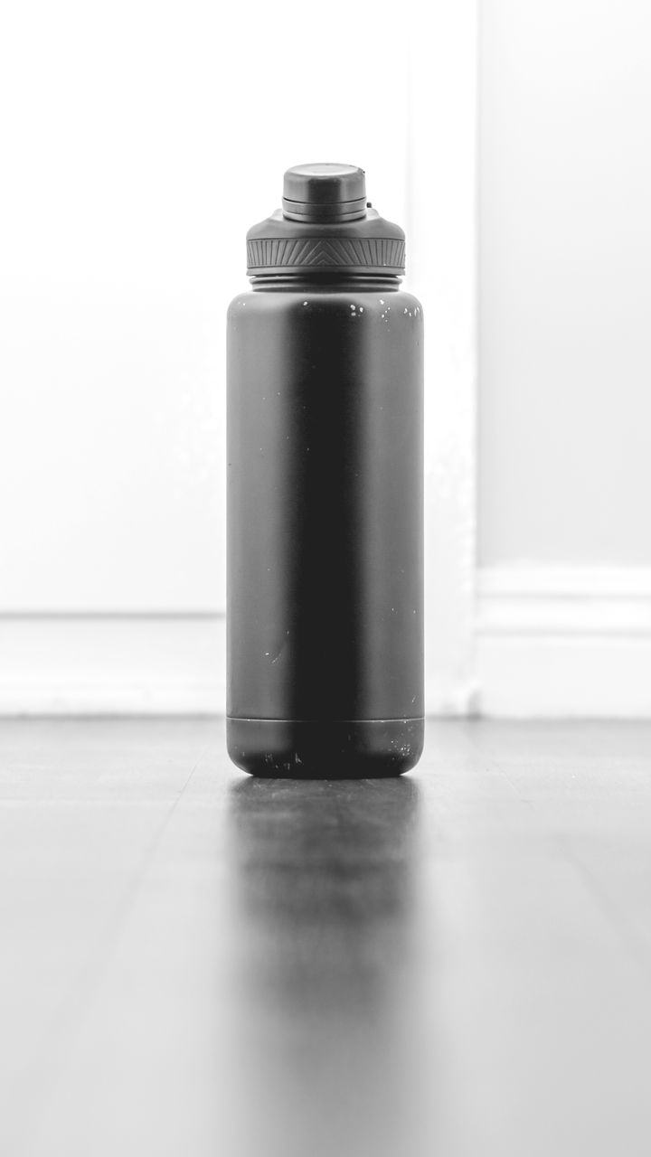 indoors, close-up, metal, still life, no people, single object, container, flooring, spray bottle, table, copy space, aerosol can, bottle, focus on foreground, equipment, white background, selective focus, surface level, can, shiny, art and craft equipment