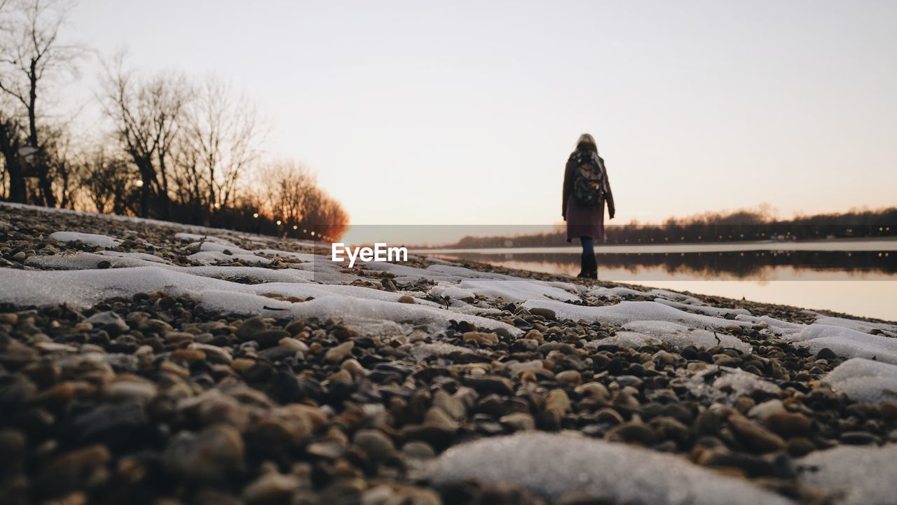 sky, snow, nature, real people, winter, cold temperature, tree, full length, lifestyles, one person, beauty in nature, sunset, water, surface level, scenics - nature, leisure activity, rear view, clear sky, tranquility, outdoors