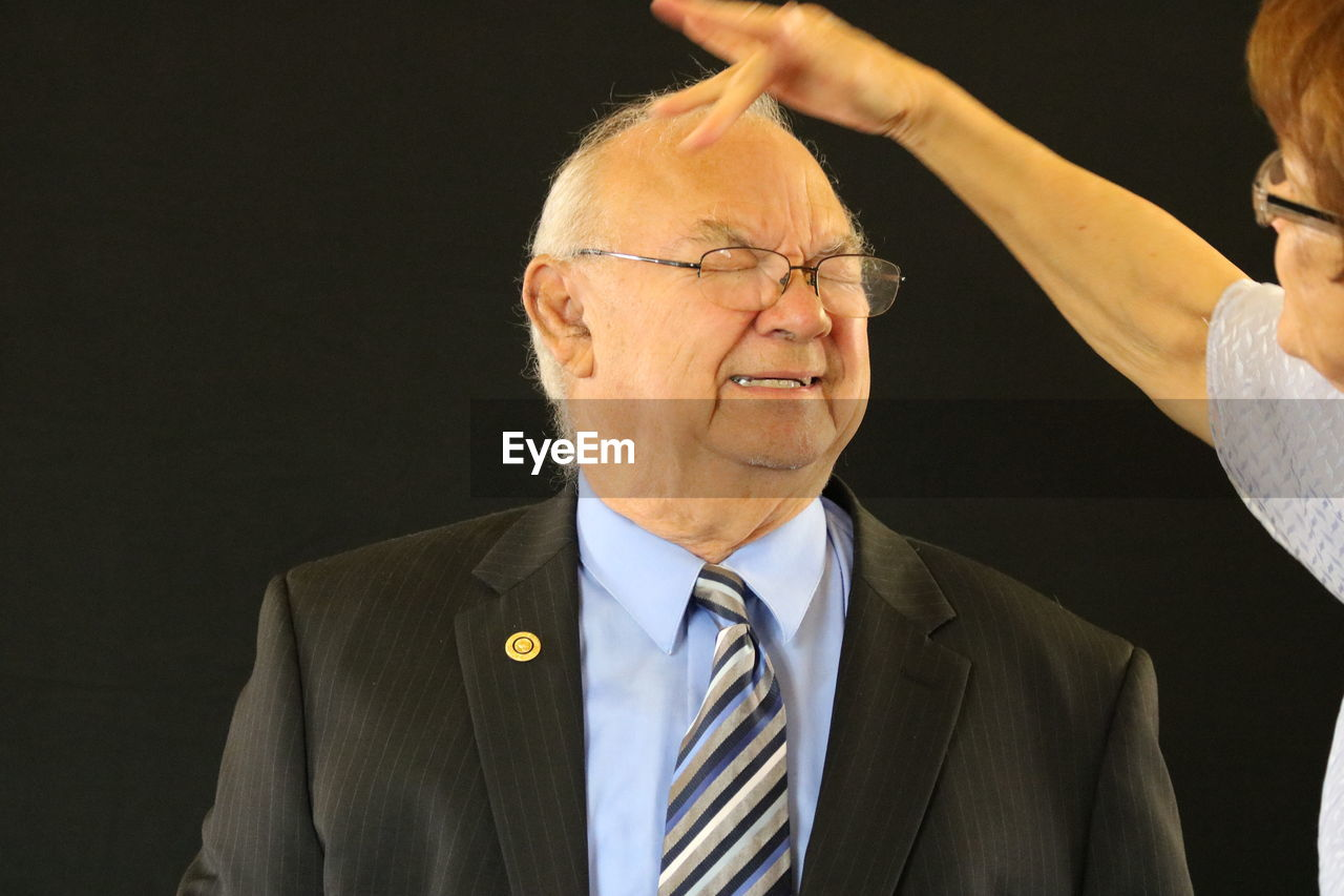 Cropped Image Of Woman Touching Head Of Senior Man Against Black Background