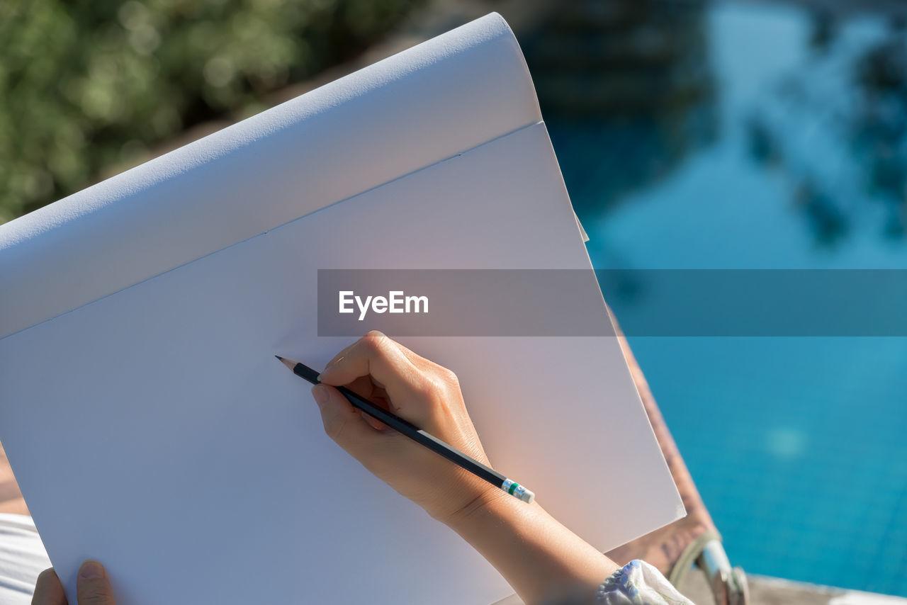 High angle view of woman drawing on easel