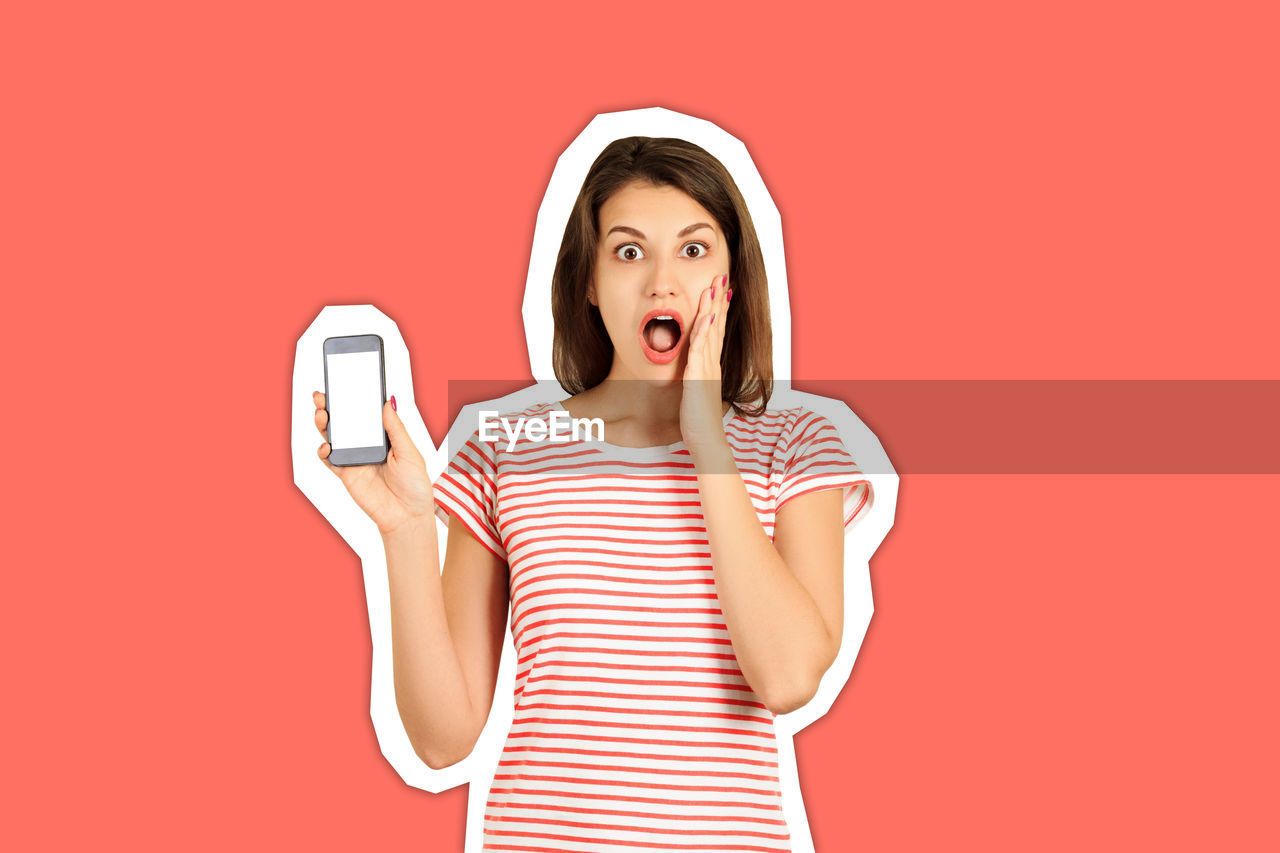 Portrait of shocked young woman showing mobile phone against orange background