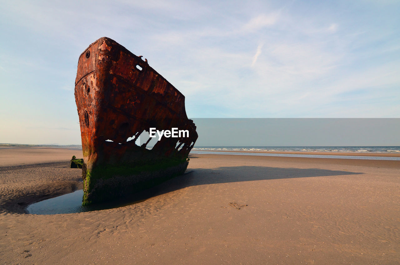 Abandoned shipwreck on beach against sky