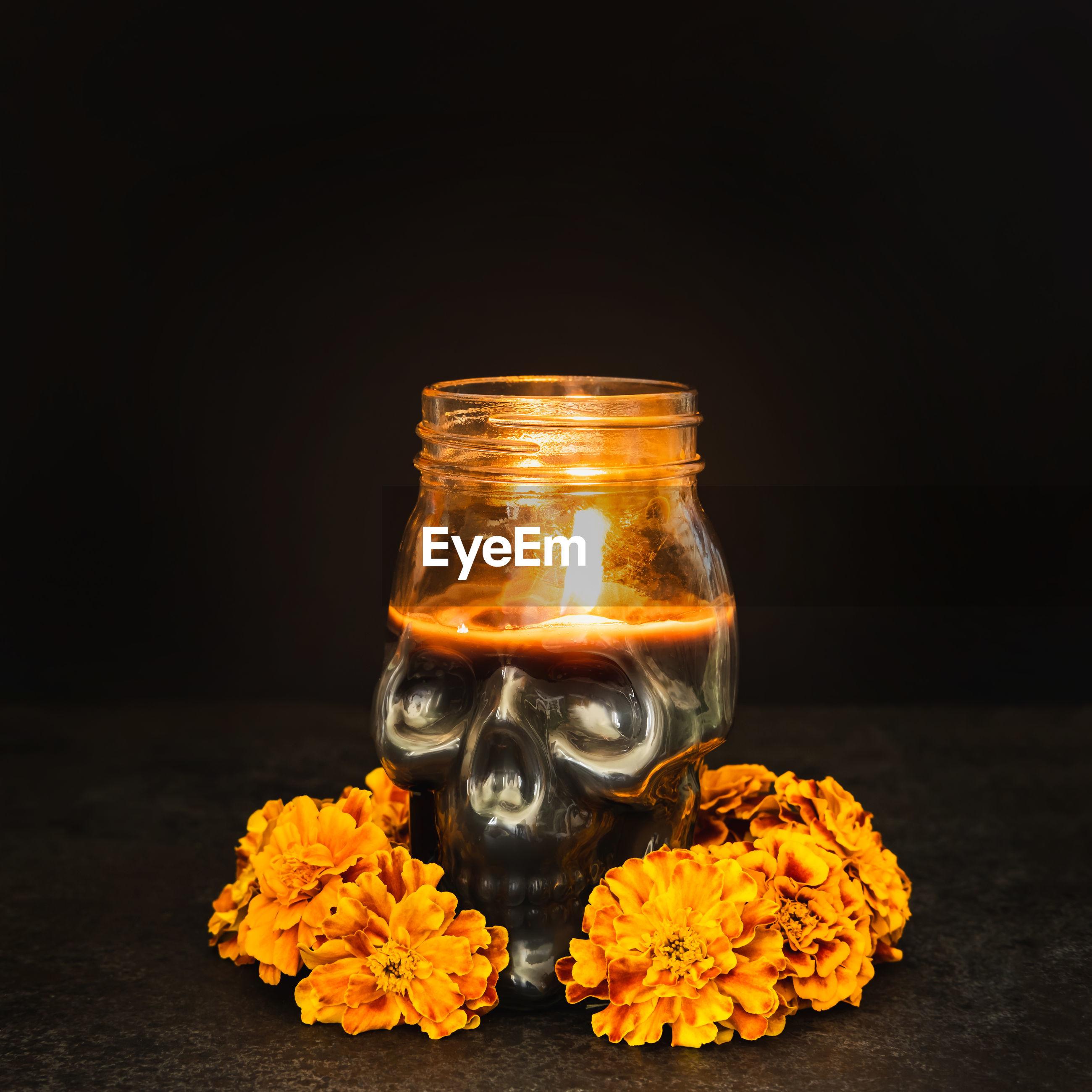 CLOSE-UP OF ORANGE FLOWERS IN JAR