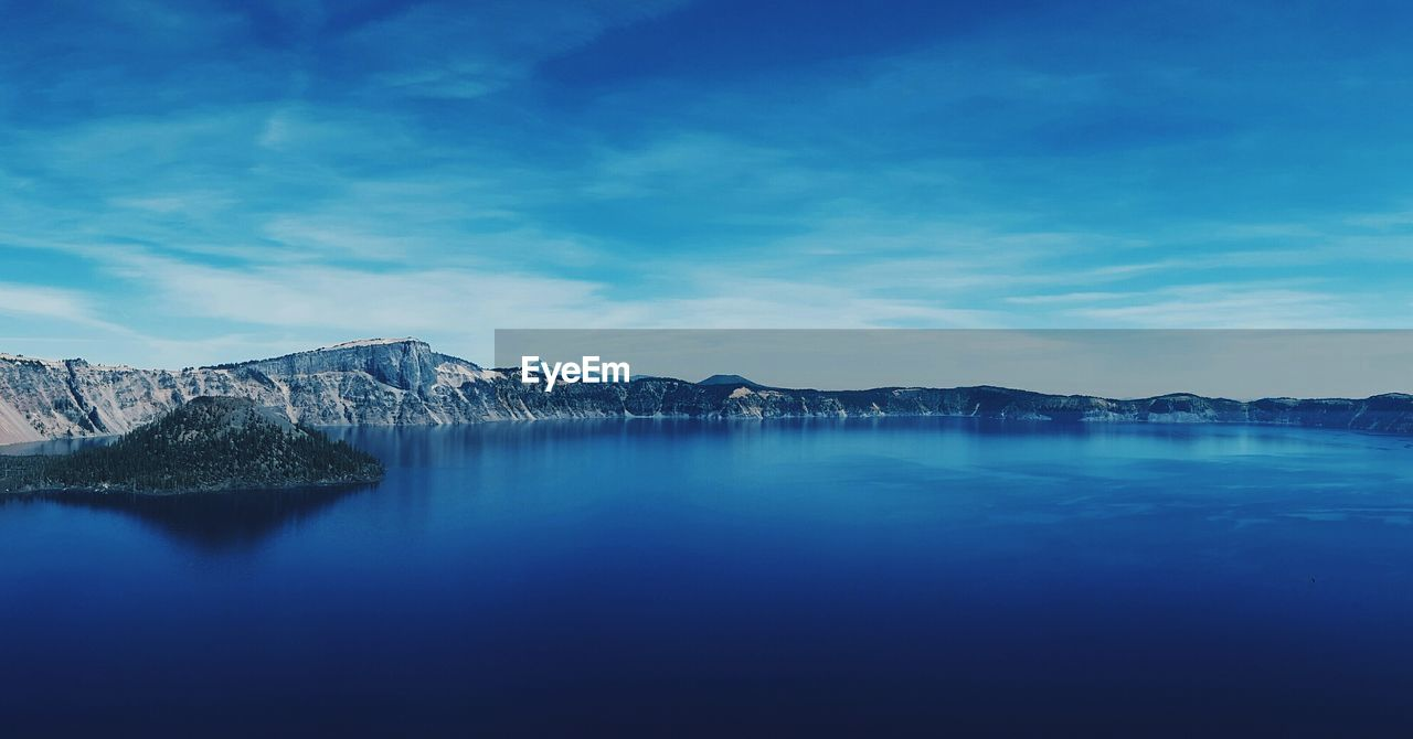 Scenic View Of Calm Crater Lake Against Blue Sky