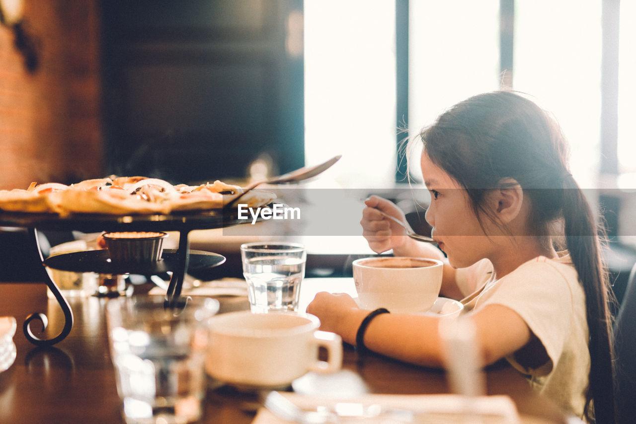 Cute Girl Eating Food In Restaurant