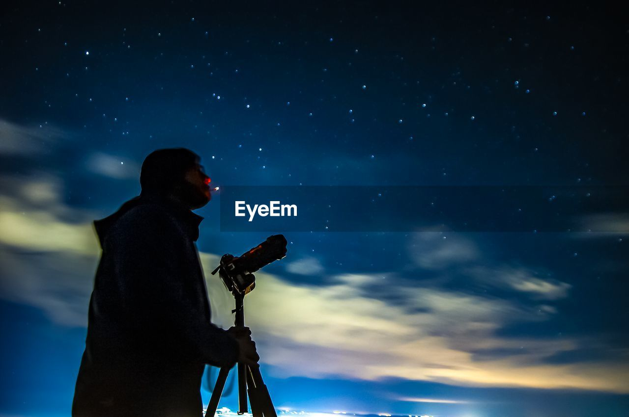 Low angle view of man photographing against sky at night
