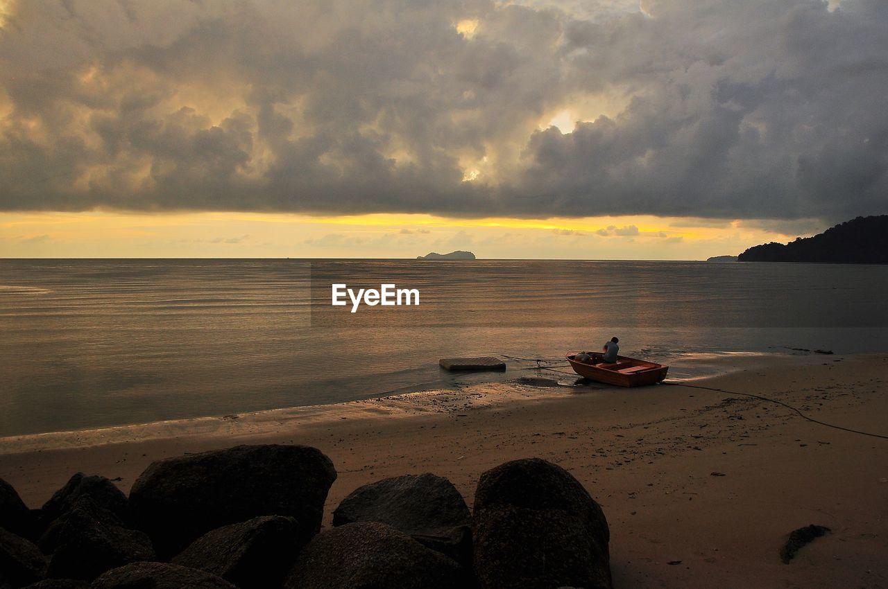 sky, water, sunset, cloud - sky, sea, beauty in nature, tranquility, scenics - nature, nautical vessel, tranquil scene, beach, nature, land, rock, horizon, idyllic, transportation, horizon over water, rock - object, outdoors