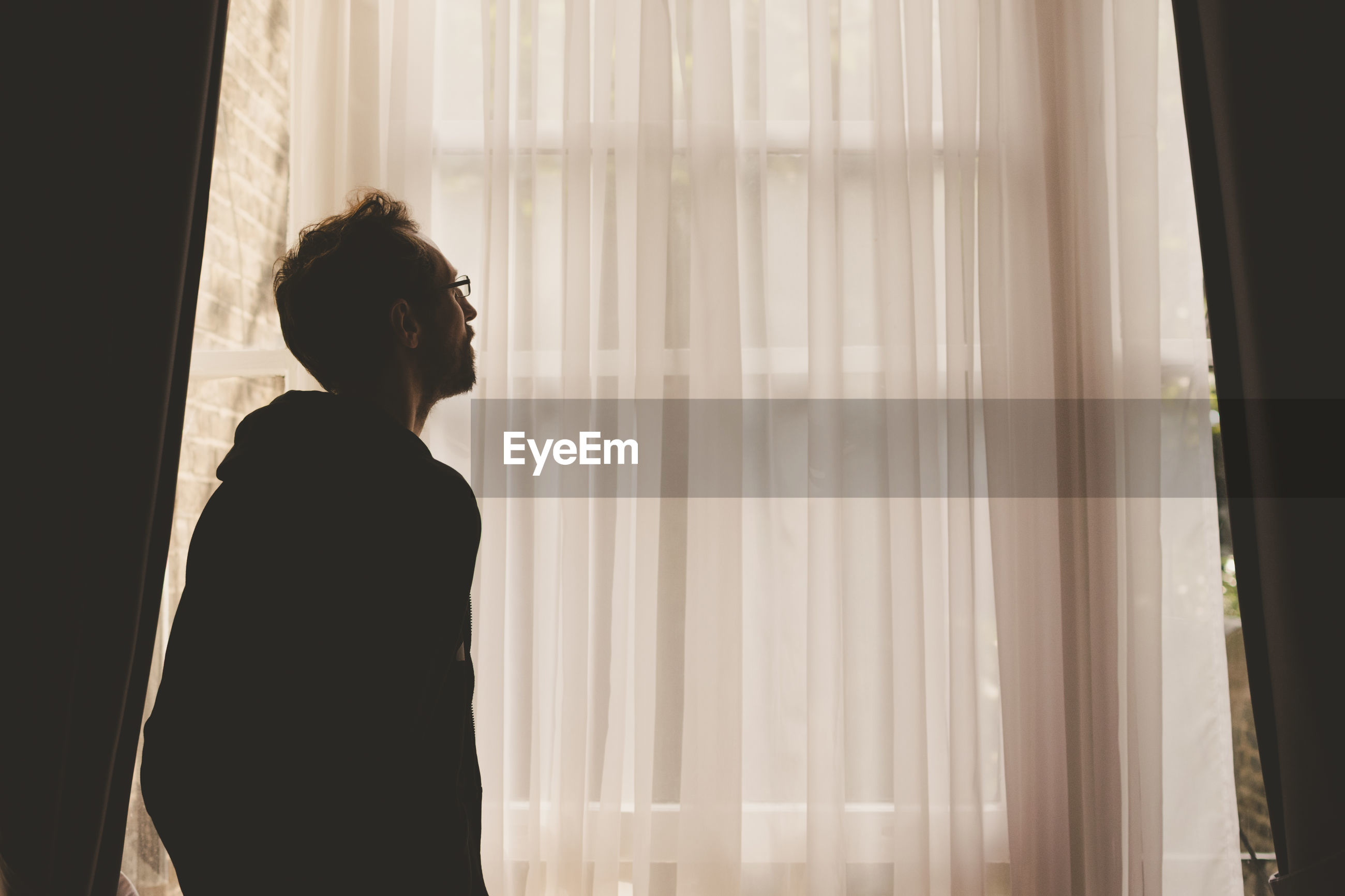 Side view of man looking through window at home