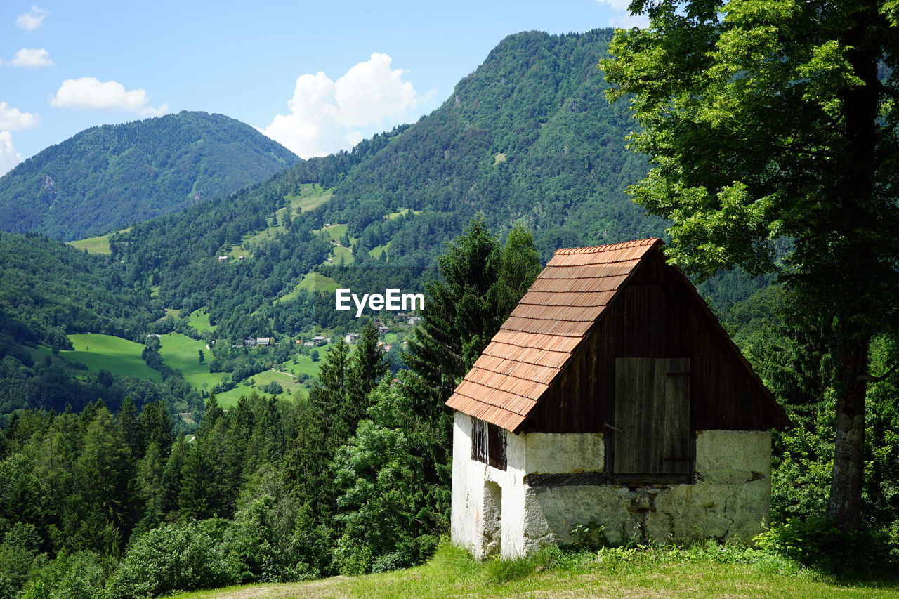 tree, mountain, architecture, plant, landscape, built structure, sky, nature, building, beauty in nature, green color, environment, no people, rural scene, scenics - nature, house, day, land, building exterior, non-urban scene, outdoors, cottage, chalet