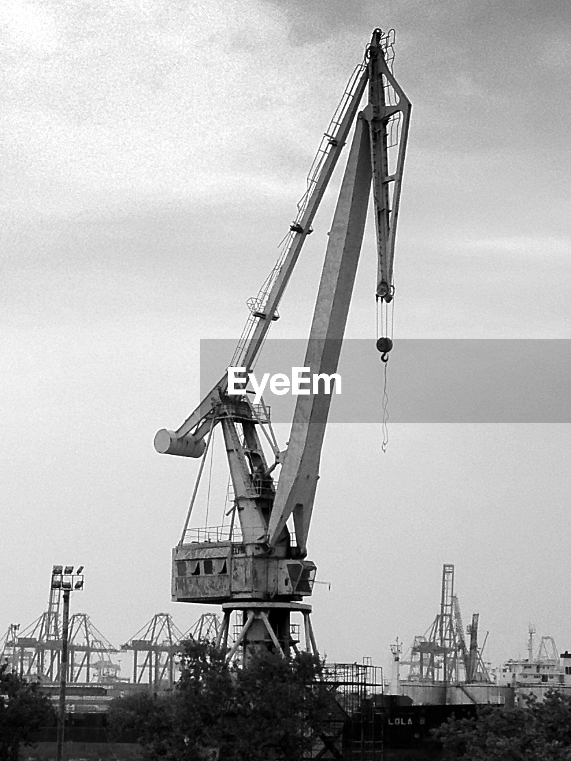 crane - construction machinery, construction site, development, sky, industry, crane, construction, construction industry, low angle view, metal, metallic, fuel and power generation, incomplete, environmental conservation, outdoors, no people, alternative energy, cloud - sky, day, wind power