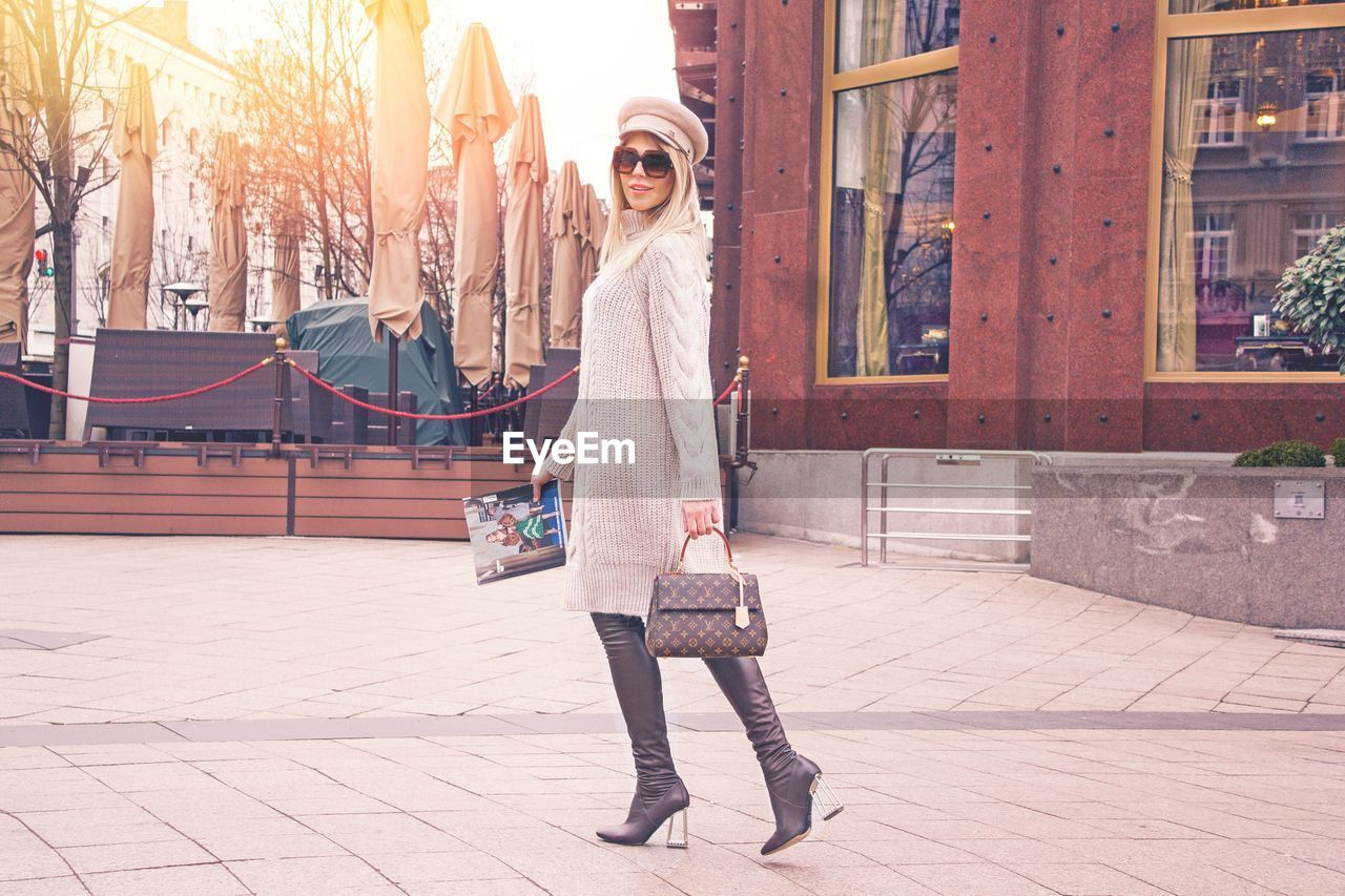 one person, full length, real people, architecture, lifestyles, building exterior, standing, city, clothing, young adult, women, leisure activity, portrait, adult, day, built structure, young women, street, fashion, warm clothing, outdoors, beautiful woman, hairstyle