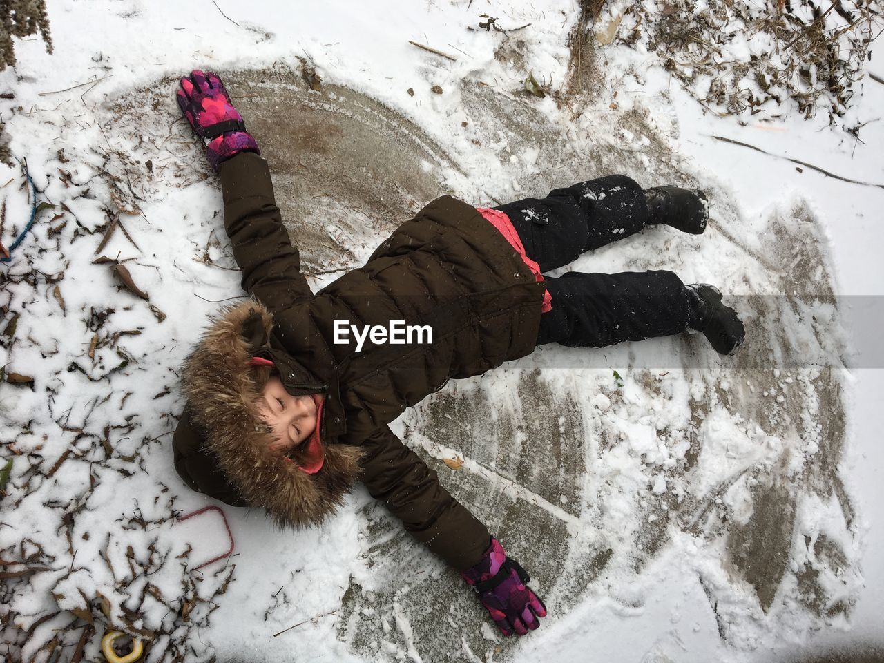 High Angle View Of Girl Making In Snow Angel