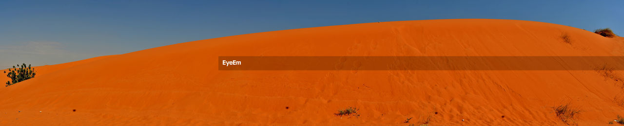 sky, scenics - nature, beauty in nature, sand dune, nature, desert, non-urban scene, landscape, tranquil scene, orange color, tranquility, remote, climate, no people, land, environment, day, sand, arid climate, mountain, outdoors