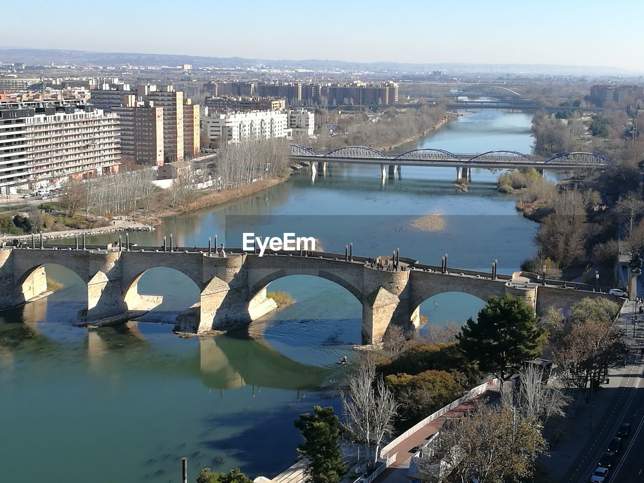 bridge - man made structure, connection, architecture, built structure, water, river, transportation, arch, day, no people, outdoors, travel destinations, city, tree, nature, building exterior, chain bridge, cityscape, sky