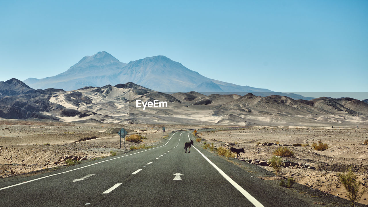 Scenic View Of Mountains In Desert With Country Road Against Clear Sky