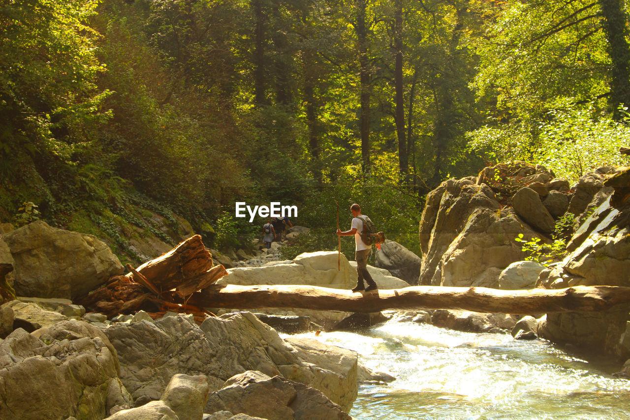 Hiker crossing lake on wooden log