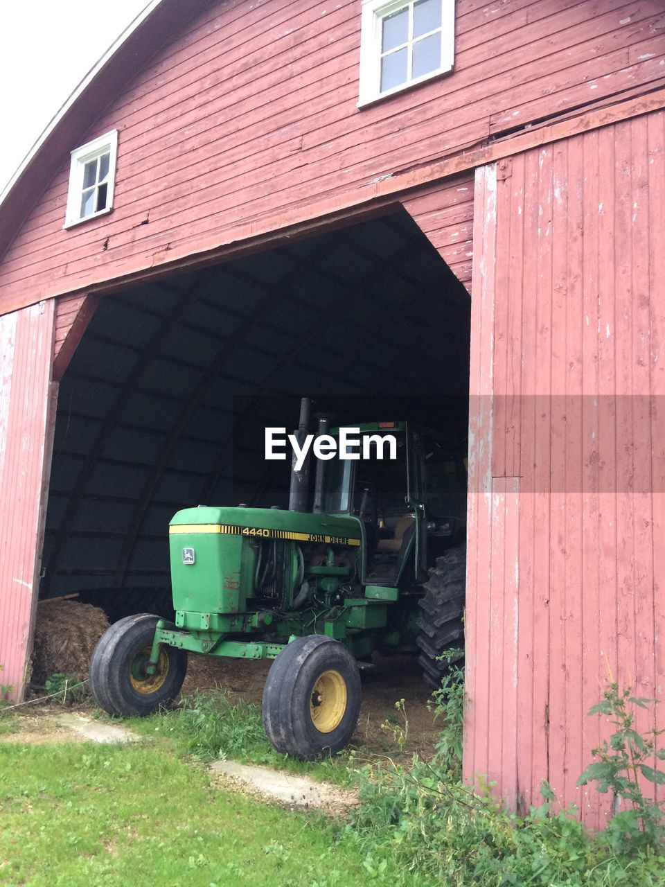 building exterior, built structure, transportation, land vehicle, architecture, mode of transportation, day, agricultural machinery, tractor, nature, land, plant, field, agriculture, grass, outdoors, agricultural equipment, no people, machinery, farm, wheel