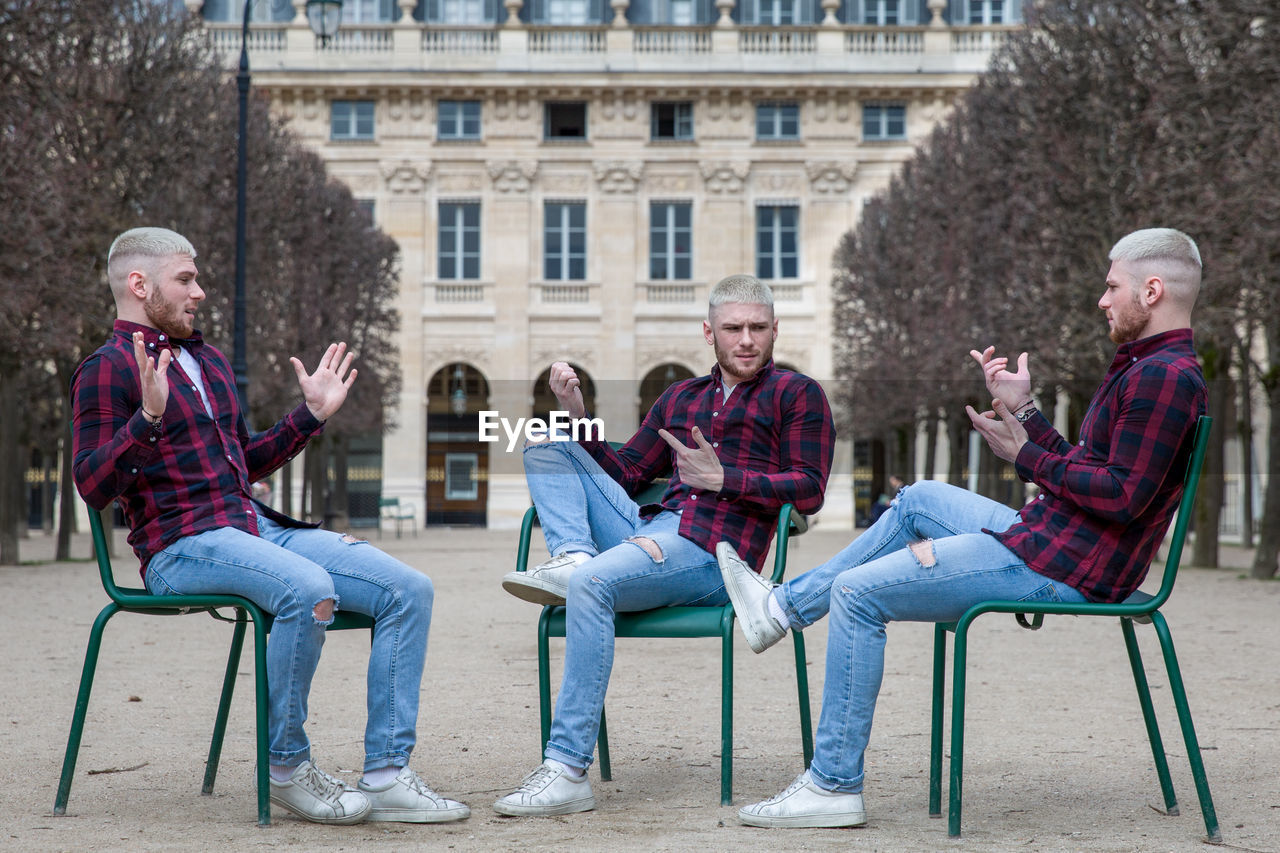 Multiple Image Of Young Man Sitting On Chairs Against Building