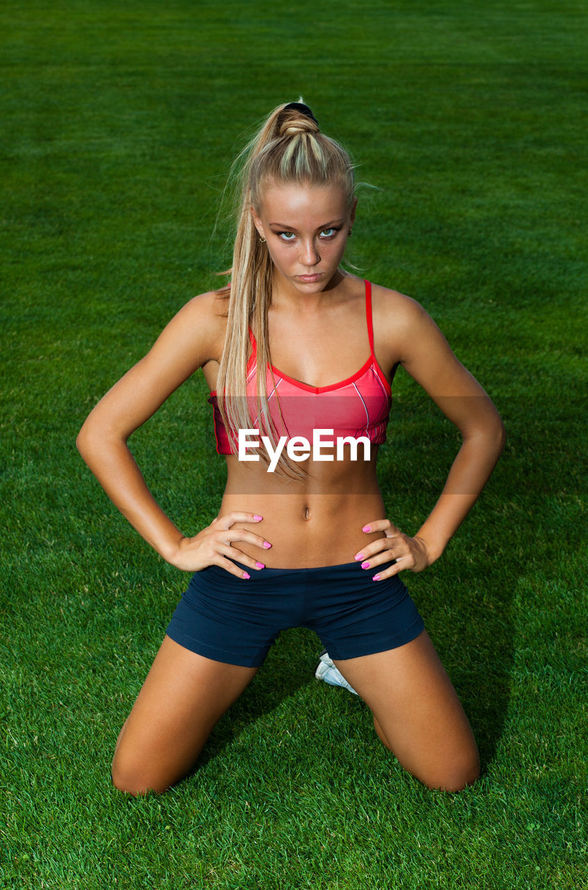 grass, one person, front view, blond hair, sport, sports clothing, green color, plant, lifestyles, exercising, hair, clothing, healthy lifestyle, day, women, nature, land, field, hairstyle, outdoors, body conscious, beautiful woman