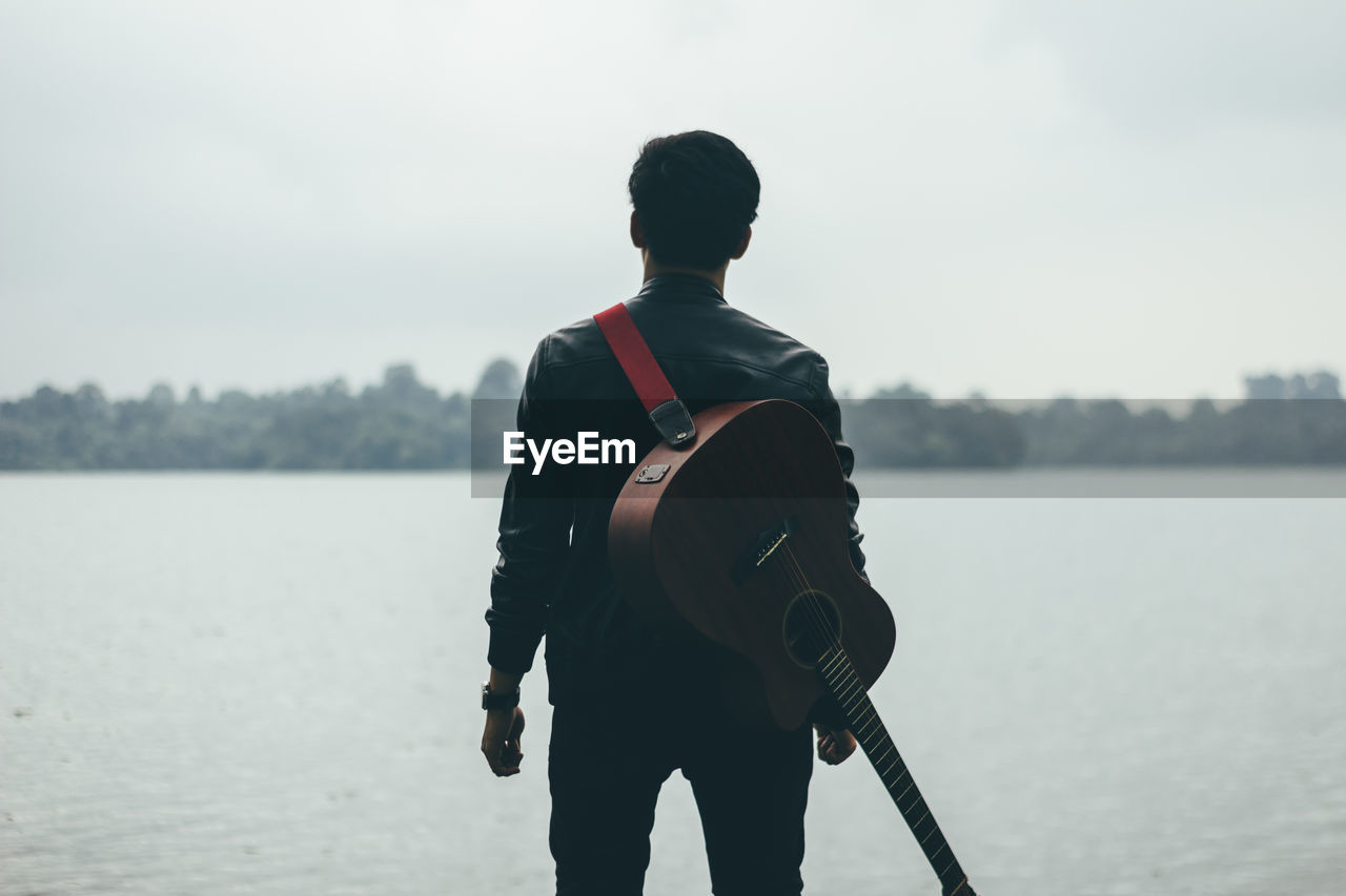 Rear View Of Man With Guitar Standing By Lake Against Sky