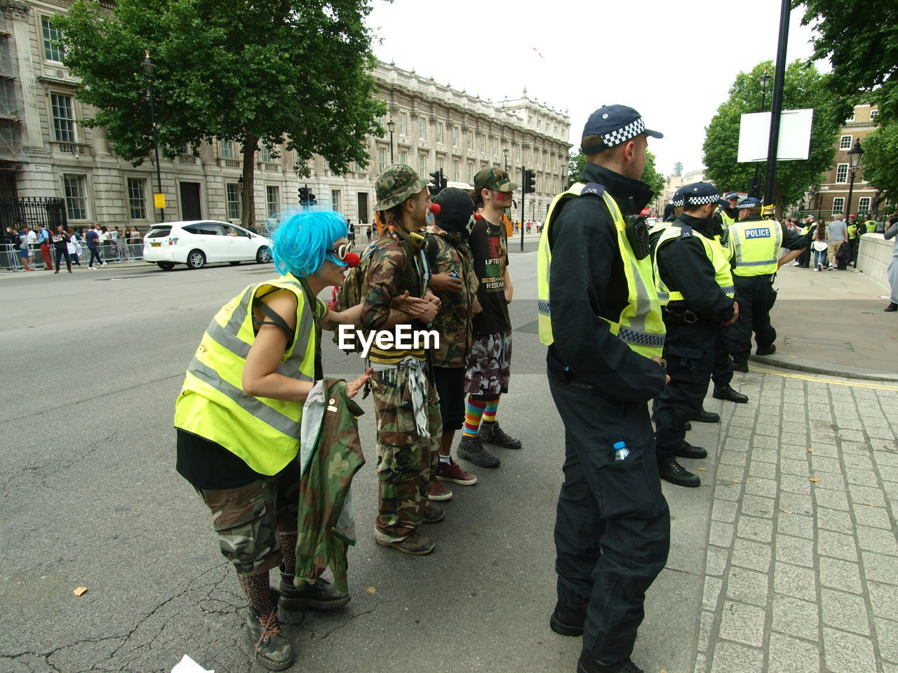 real people, building exterior, full length, street, men, reflective clothing, architecture, built structure, large group of people, walking, day, responsibility, women, city, helmet, outdoors, land vehicle, standing, road, togetherness, lifestyles, tree, police force, headwear, police uniform, hardhat, sky, adult, people