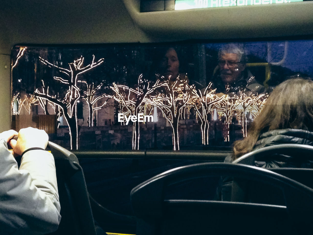 REAR VIEW OF MAN AND WOMAN IN BUS