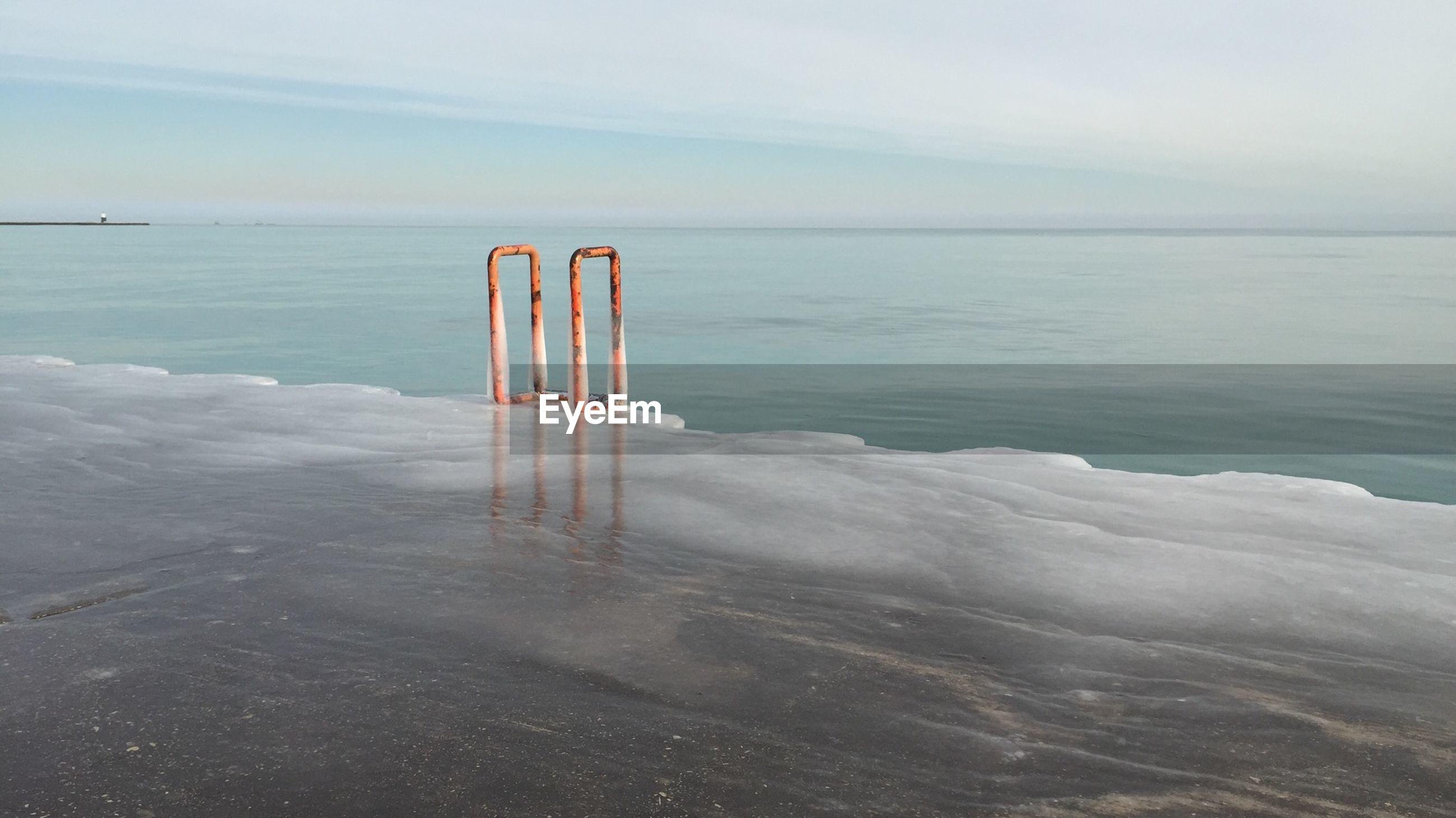 Rail on frozen pier by sea against sky