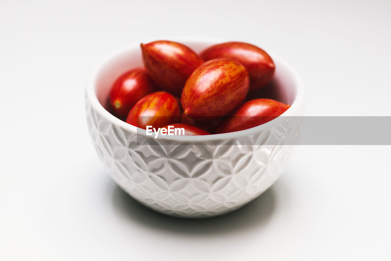 food, food and drink, studio shot, freshness, still life, fruit, bowl, wellbeing, indoors, white background, red, close-up, healthy eating, no people, cut out, table, large group of objects, container, group of objects, abundance, ripe
