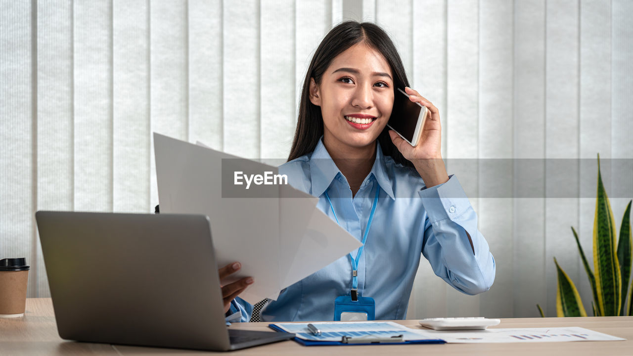 PORTRAIT OF WOMAN WORKING ON TABLE IN OFFICE