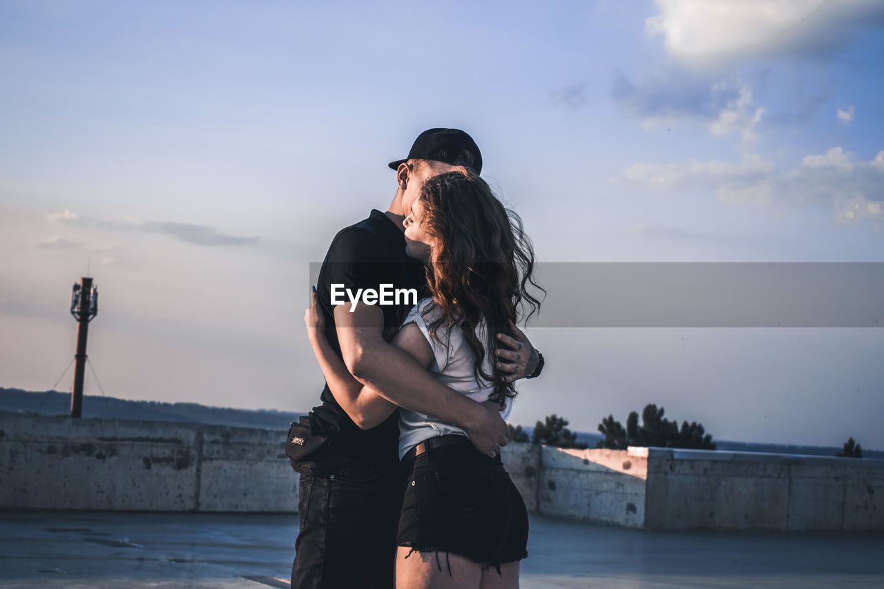 Couple Embracing While Standing On Terrace Against Sky