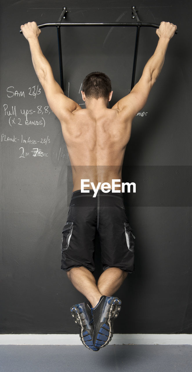 REAR VIEW OF SHIRTLESS MAN WITH HANDS