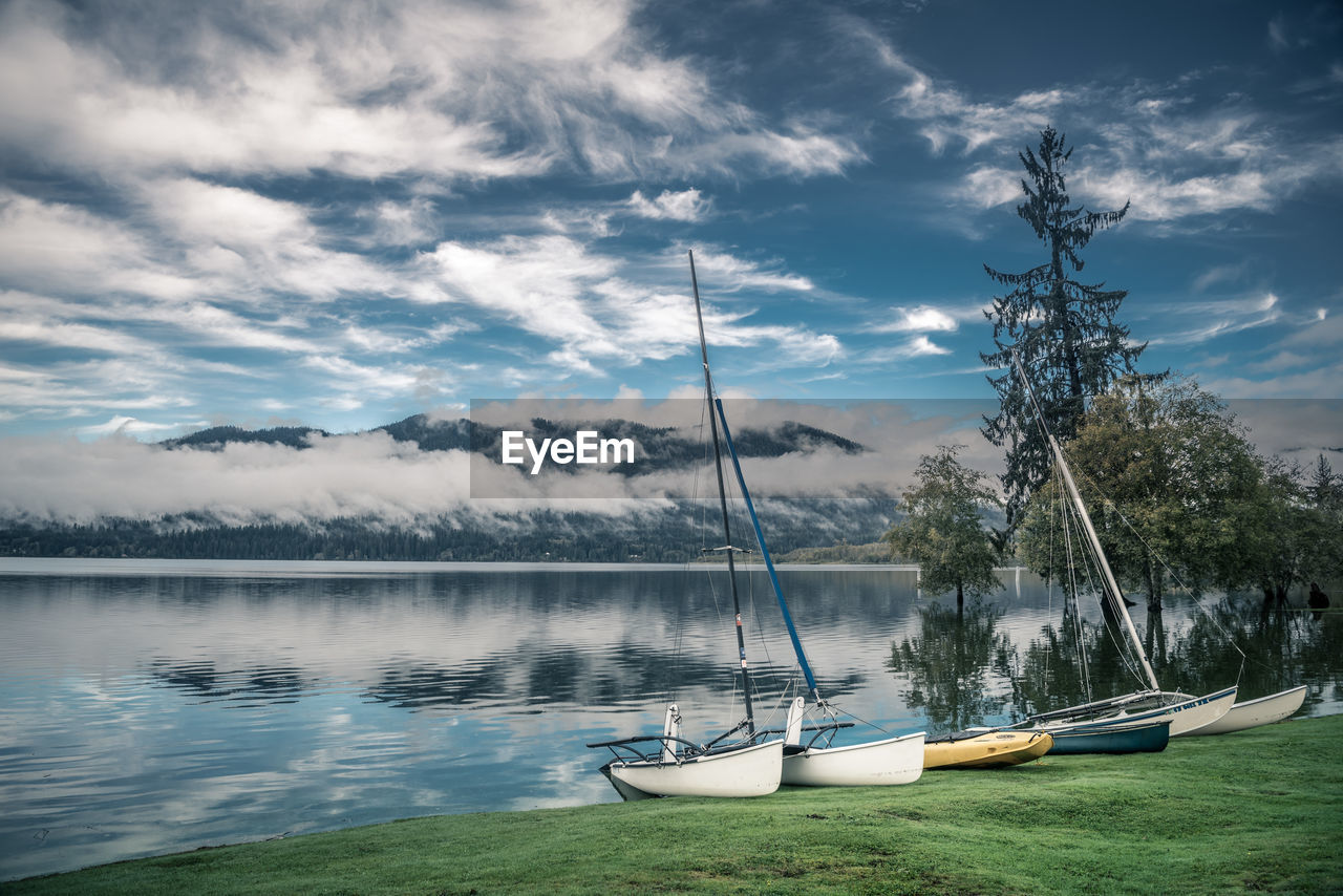 Boats by calm lake against cloudy sky