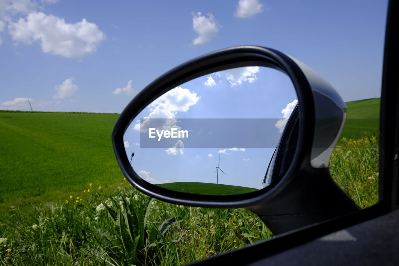 Reflection of windmill in side-view mirror of car on grassy field