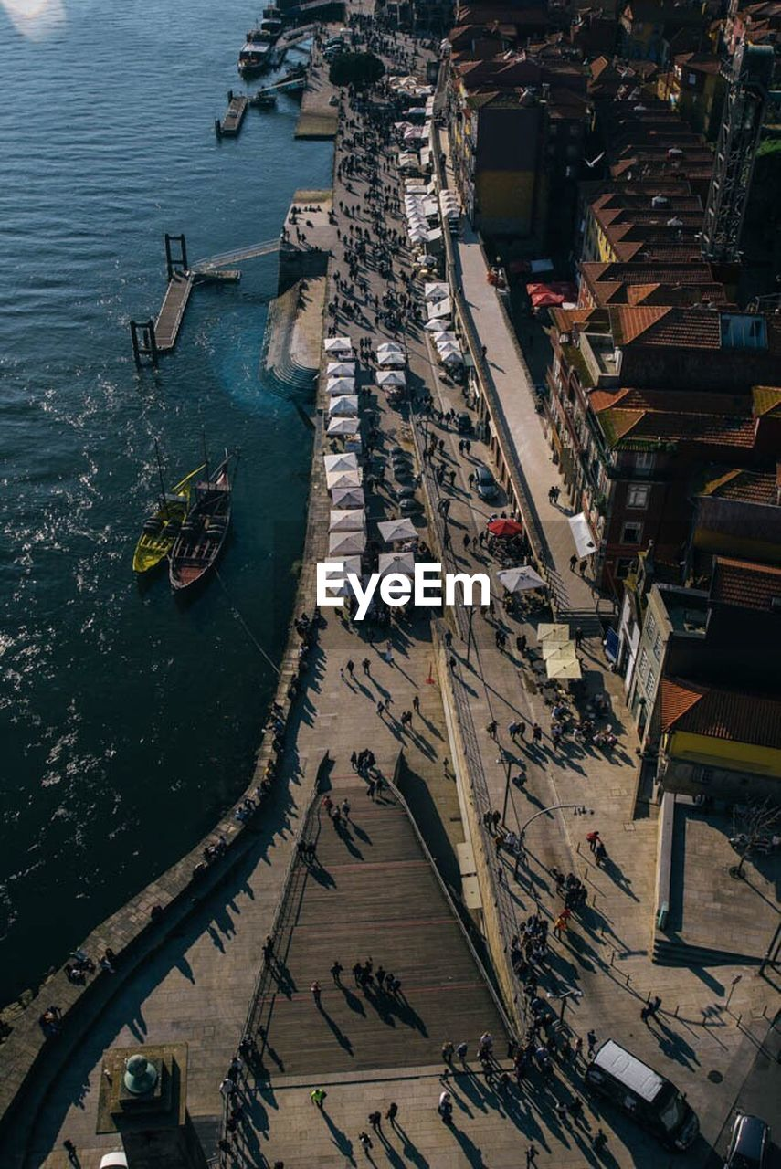 high angle view, nautical vessel, transportation, day, outdoors, mode of transport, architecture, freight transportation, aerial view, sea, built structure, building exterior, water, city, large group of people, cityscape, people