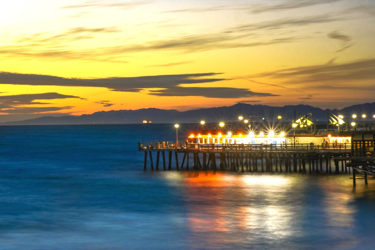 sky, water, sunset, sea, scenics - nature, beauty in nature, cloud - sky, waterfront, tranquil scene, orange color, tranquility, illuminated, nature, reflection, idyllic, no people, architecture, pier, built structure, horizon over water, outdoors, wooden post